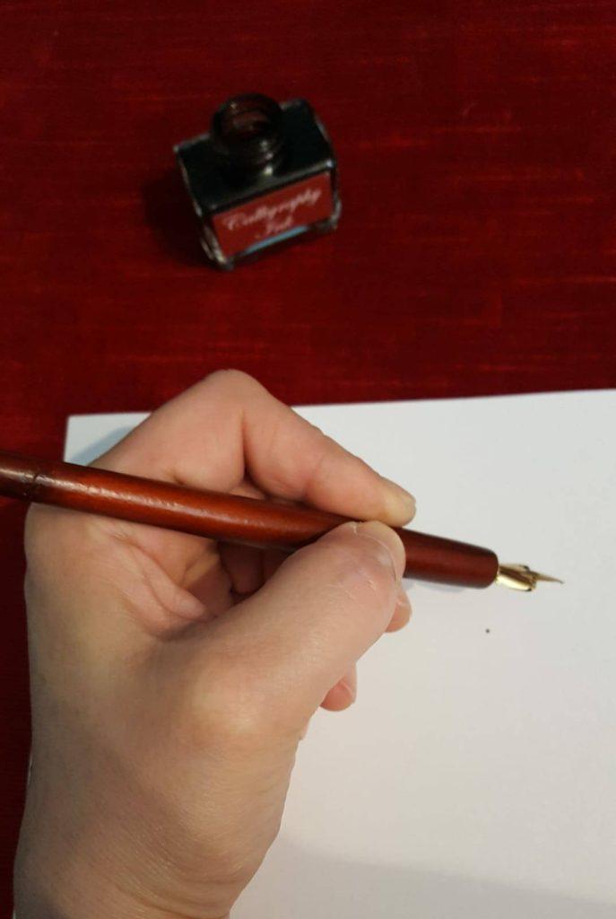 Hand mit Füller, deutet Schreiben an.